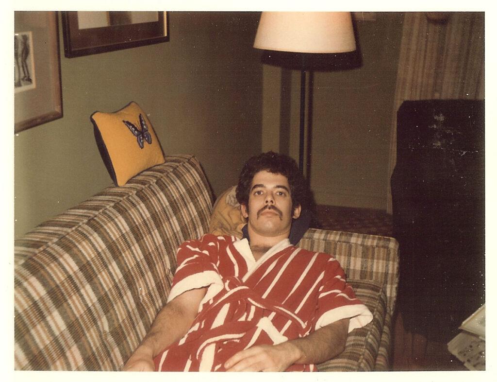 Ein junger Mann mit rot-weiß gestreiftem Bademantel liegt auf einem Sofa. 60er Jahre Stil.