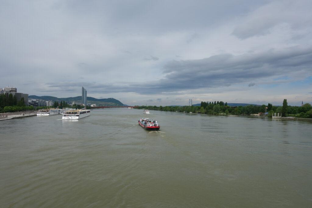Ein Schiff fährt auf der Donau. Ausblick von der Reichsbrücke in Wien in Richtung Nussdorf.