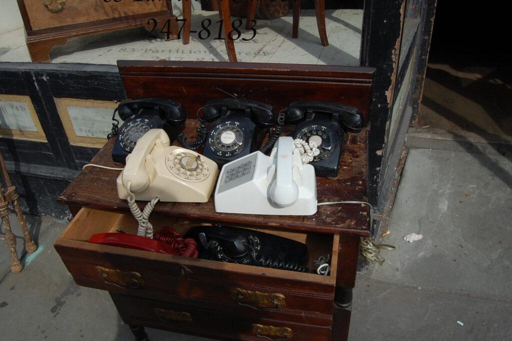 Mehrere alte Tasten- und Wählscheibentelefone stehen auf einem Möbelstück mit Laden außerhalb eines Aniquitätengeschäfts in New York City.