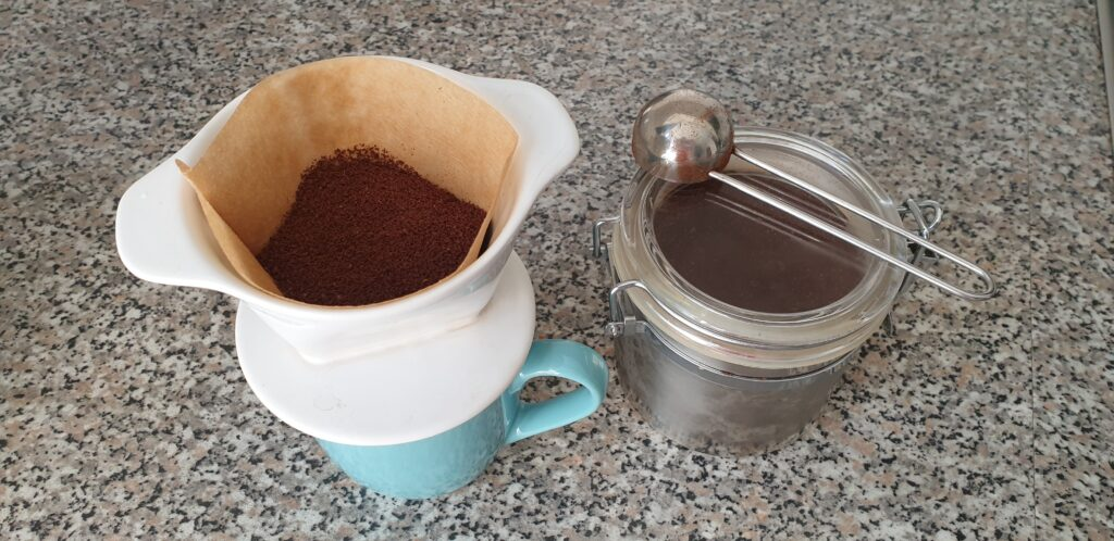 Kaffeetasse mit Keramikhandfilter und Kaffeebehälter