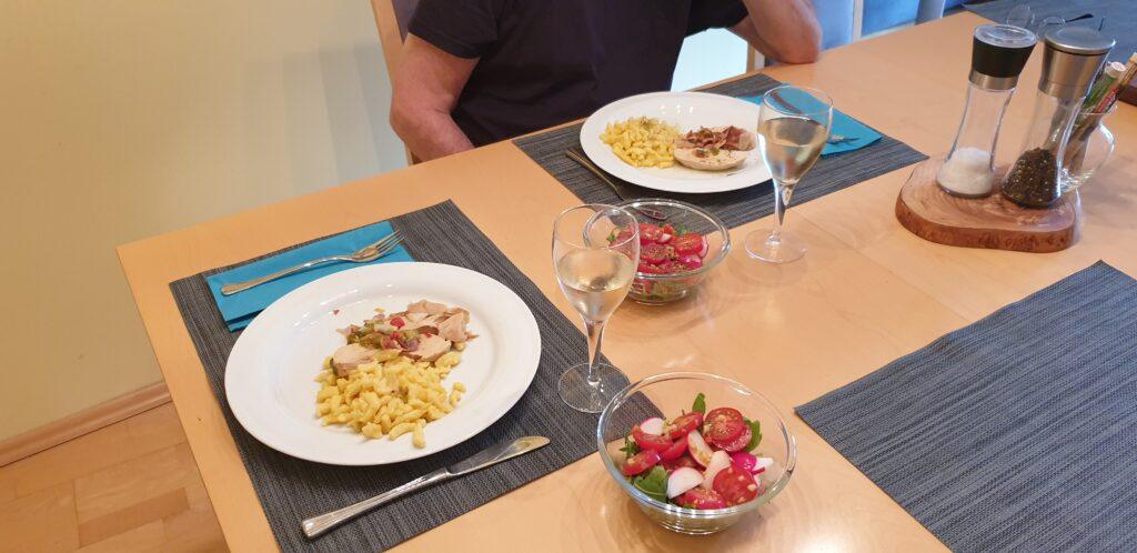 Tisch mit 2 Tellern mit Putenbraten und Spätzle, Salat und Weißwein.