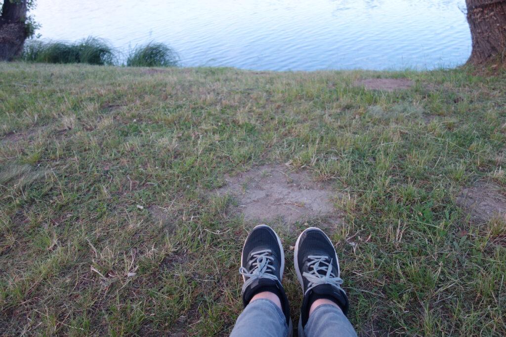 Füße ausgestreckt auf einer Parkbank mit Blick auf die Alte Donau. 12 von 12 geht zu Ende.
